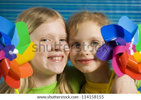 Children with rainbow pinwheel on a striped blue background