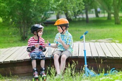 children with rollers and scooter sit on a wooden platform in the park