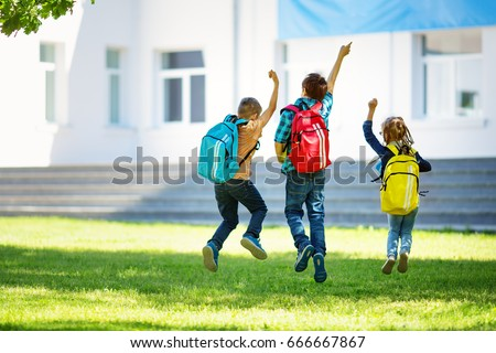 Children with rucksacks jumping in the park near school. Pupils with books and backpacks outdoors