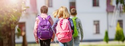 Children with rucksacks standing in the park near school. Pupils with books and backpacks outdoors