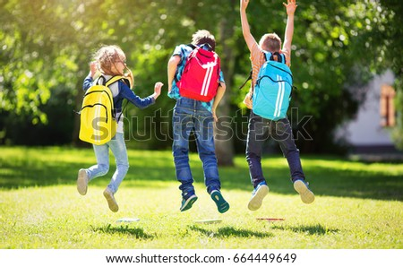 Children with rucksacks standing in the park near school. Pupils with books and backpacks outdoors #664449649