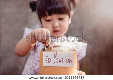 Children with Saving Money for Education Concept. 2 Years Old Child putting Coin into a Box
