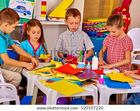 Children with teacher are making something out of colored paper on table in primary school. Children craft lesson in primary school.