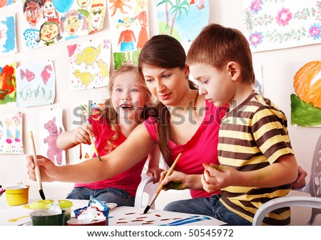Children  with teacher draw paints in play room. Child care.
