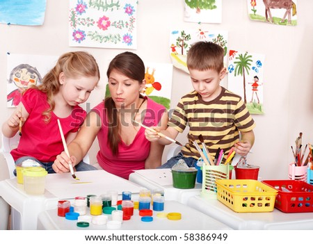 Children with teacher painting in play room. Preschool.