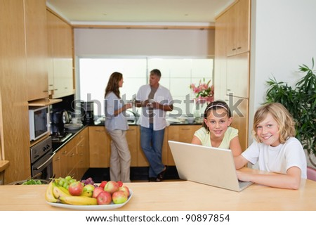 Children with their notebook in the kitchen and parents behind them