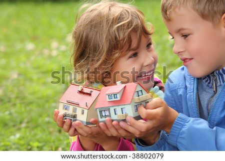 children  with toy small houses in hands outdoor