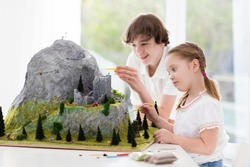 Children work on model building school project. Kids build miniature scale model mountain for geography class. Extracurricular activities and hobby club. Art and crafts for teenager and preschool