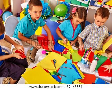 Children working with colored paper on table in kindergarten .Creative development of children.
