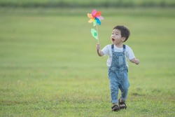 Childrens colorful windmill toy. laughing kid happily playing. Little boy blows against a colorful windmill in summer at summer camp in the sunshine.