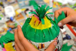 childrens hands are making a pinata with colorful paper
