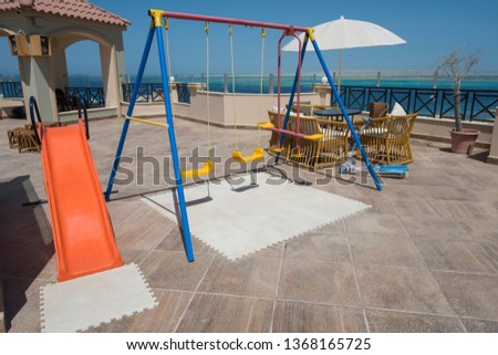 Childrens play area playground on large roof terrace patio area with panoramic tropical sea view #1368165725