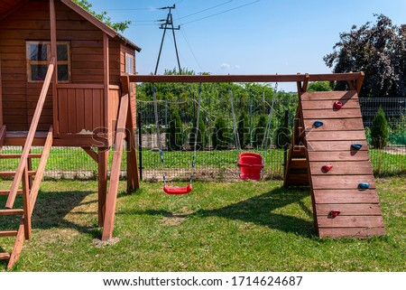 Childrens playground by the house garden, visible wooden house, beautiful spring day. Foto stock ©