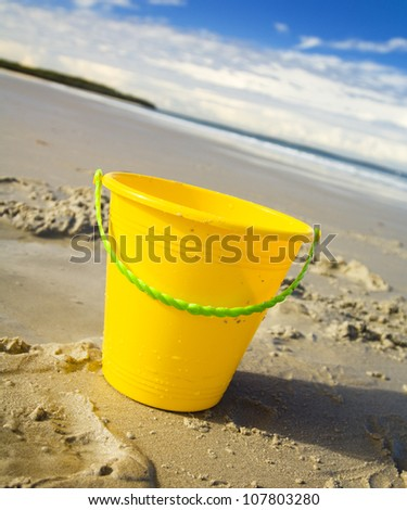Childrens toy bucket in the sand at the beach