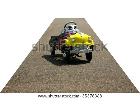 childs generic pedal car on a city street, cropped with the road as the vanishing point on white