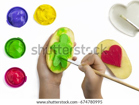 Childs hand, play painting with potato stamps, brushing green on a figure shape, red ,yellow, and purple poster paints  some isolated objects on a white background, copy space