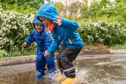 Childs in rainy day. Cute happy kids boys is jumping in the puddle. Bright spring rainy day. Kid in yellow rubber boots and rain suit, raincoat. Brothers outdoors.