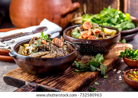 Chilean Ajiaco. Latin American food. Ajiaco - traditional chilean soup with grilled meat, onion and potato served in clay plates.