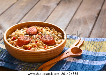 Shutterstock Chilean dish Porotos con Riendas (in English beans with reins) made of beans, linguine (flat spaghetti), fried sausage, photographed with natural light (Selective Focus, Focus one third into the dish)
