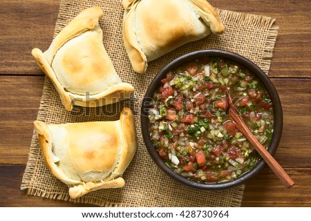 Chilean Pebre sauce, a traditional condiment made of tomato, onion, garlic, spicy aji pepper and coriander with empanadas on the side, photographed overhead on dark wood with natural light