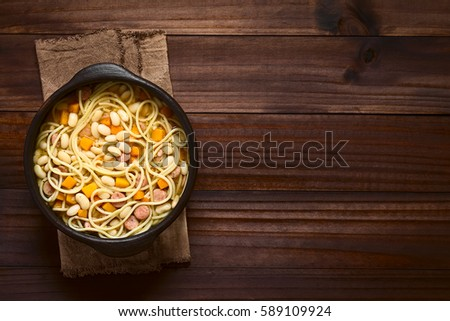Chilean traditional Porotos con Riendas (beans with reins) dish of dried beans with pumpkin, onion, spaghetti and sausage, served in rustic bowl, photographed overhead on dark wood with natural light