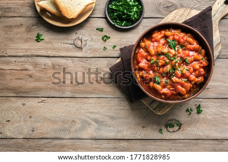 Chili Beans on wooden table, top view, copy space. Homemade stewed vegan vegetarian recipe with kidney beans and vegetables.