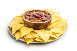 Chili con carne and tortilla chips on plate. Mexican food with beans in wooden bowl isolated on white background.