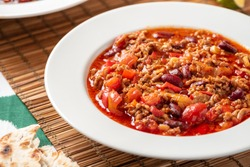 Chili con carne in a white bowl on a served table close-up. Chili con carne - a traditional Mexican soup with beans, tomatoes, minced meat and hot peppers. Mexican cuisine.