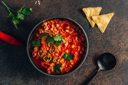Chili Con Carne in bowl with tortilla chips on dark background. Mexican cuisine. Top view