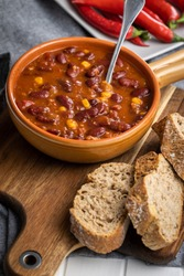 Chili con carne. Mexican food with beans in pot and bread on cutting board.