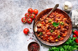 Chili con carne - minced meat stew with red bean and tomato in a clay bowl on a light grey slate, stone or concrete background.Traditional dish of mexican cuisine.Top view with copy space.