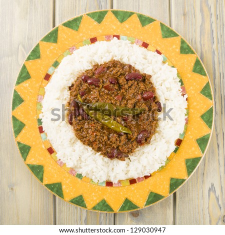 Chili con Carne - Spicy minced beef stew with chilies and beans served over boiled rice. Overhead shot.