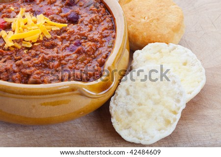Chili Con Carne topped with shredded cheddar cheese, and served with hot buttered biscuits.