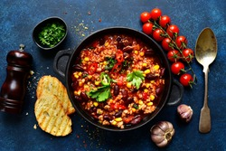 Chili con carne - traditional mexican minced meat and vegetables stew in tomato sauce in a cast iron pan on a dark blue slate, stone or concrete background. Top view with copy space.