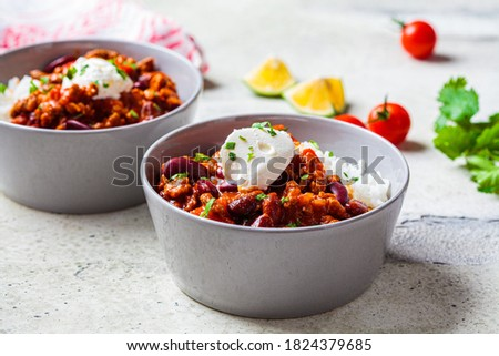 Chili con carne with rice in a gray bowl. Beef stew with beans in tomato sauce with sour cream and rice. Traditional Mexican food concept. Foto stock ©