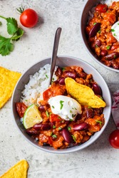 Chili con carne with rice, sour cream and nachos in a gray bowl. Beef stew with beans in tomato sauce with sour cream and rice. Traditional Mexican food concept.