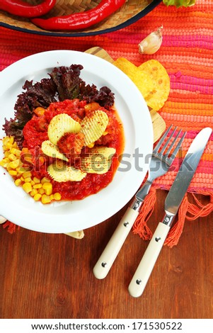 Chili Corn Carne - traditional mexican food, on white plate, on napkin, on wooden background