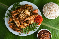 Chili crab curry or Kerala crab roast and red Matta rice popular hot and spicy seafood dish India, Sri Lanka, Singapore. cooked in roasted coconut sauce. on white plate green banana leaf background.
