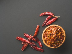 Chili flakes in the wooden bowl and dried peppers on black papper background. Dried and crushed fruits of Capsicum frutescens, used as hot spice and for tabasco sauce. Top view. Copy space.