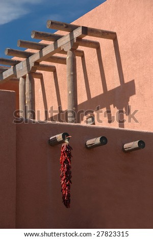 Chili peppers hanging on typical southwestern architectural building. New Mexico.