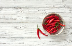 Chili peppers in clay pot over white wood background. Top view. Copy space