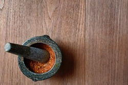 Chili peppers in stone mortar on wooden background.