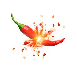 Chili powder and chili flakes burst out from red chili pepper over white background