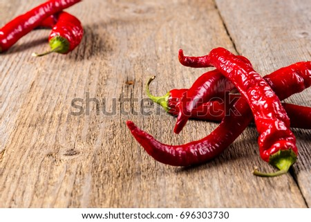 Chili. Red chili peppers on wooden table. Selective focus. #696303730