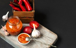 Chili sauce, tomatoes and hot red pepper on a wooden background, rustic style.