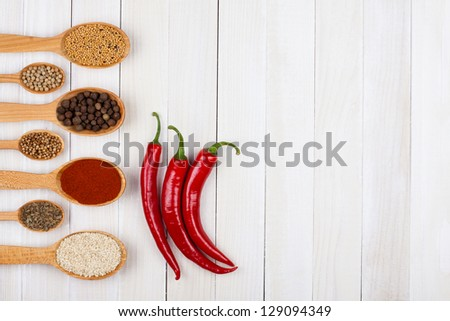 Chili, spices in wooden spoons on wood background