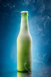 Chilled beer bottle on blue background