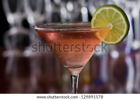 chilled cosmopolitan cocktail served in a  martini glass on a busy bar with a shallow depth of field with blurred glasses and lights in the back, garnished with a lime