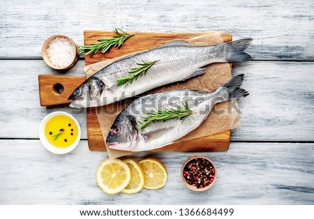 chilled raw fish sea bass and Dorado with ingredients on a cutting board on a wood background Photo stock ©