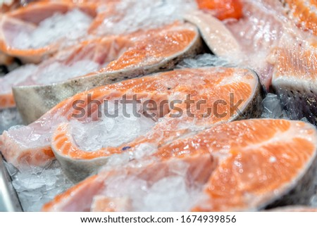 Chilled steaks of red fish. Pieces of fish lie on ice. Freezer shop window. Chilled steaks of red fish. Pieces of fish lie on ice. Freezer shop window. Close-up photo.